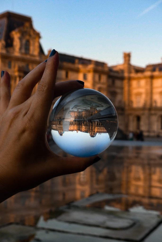A hand holding a glass ball, with a building in the background. The image of the building in the ball is upside down