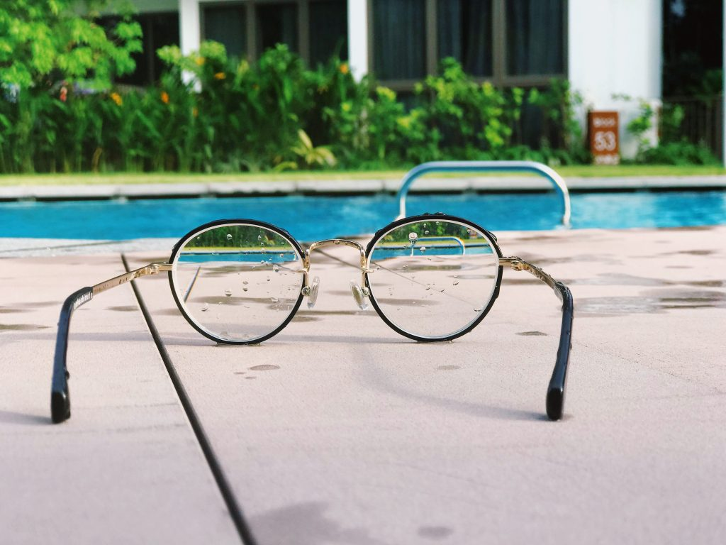 An image of a swimming pool, with glasses in  front. Through the glasses we see the same image again.